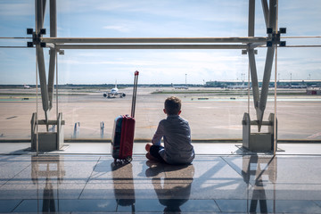 a child at the airport looking at the runway with aircrafts