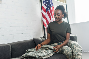 Female army soldier folding camouflage clothes on sofa