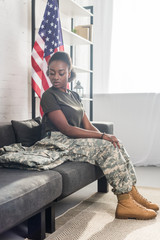 Attractive woman in camouflage clothes sitting on sofa