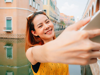 Woman tourist is taking selfie photo from the smartphone.