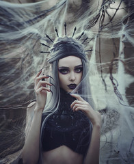 Beautiful sexy Gothic girl with pale skin and long white hair like spider black widow in spider web. Dark Princess with long vampire claws in the crown. Spider woman weaving net. Gothic look.