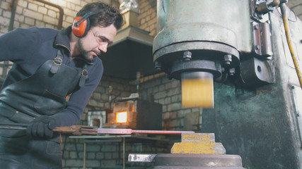 Molten metal is processed under pressure in the hands of a blacksmith