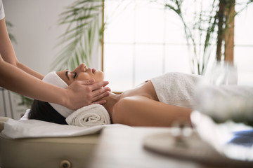 Pleasant procedure. Delighted pleasant woman lying and enjoying a professional massage
