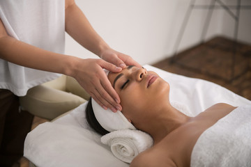 Professional massage. Calm relaxed woman being in the spa salon while enjoying the massage procedure
