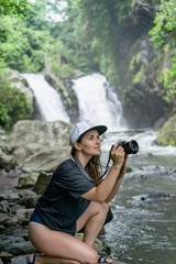 side view of woman in cap with photo camera in hands and Aling-Aling Waterfall on backdrop, Bali, Indonesia