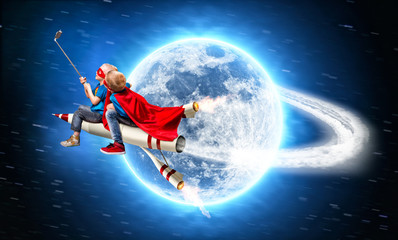 Children in superhero costumes fly in space on a rocket  and shoot a selfie on a mobile phone.