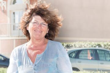 happy senior woman retired in street shower in wind