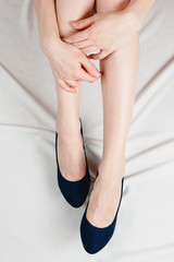 Above shot of white woman holding her legs in a high heeled dark blue shoes sitting on bed with white sheets.