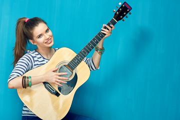 Teenager girl play music on guitar.