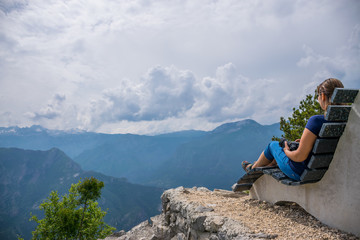 The girl photographer is resting on the top of the mountain sitting on an unusual bench.