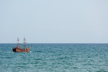 a wooden pleasure boat with masts, made under the old days, floats in the sea