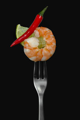 Big tiger prawn / shrimp with lime and red chilli pepper on black isolated background.