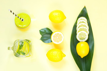 Summer lemon composition for cooking detox lemonade with mint and ice in mason jar on yellow. Tropical concept. Top view. Flat lay.