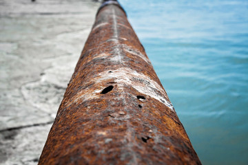 An old rusty pipe with holes close up.