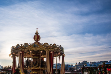 Vintage carousel ride spins in the air at sunset