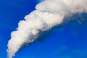 smoke from a pipe in the factory against a blue sky
