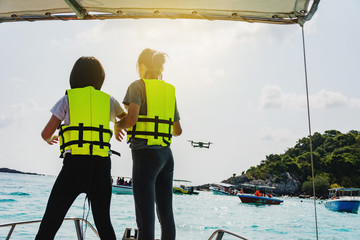 Kids standing on speed boat, try to control flying drone with waving hand