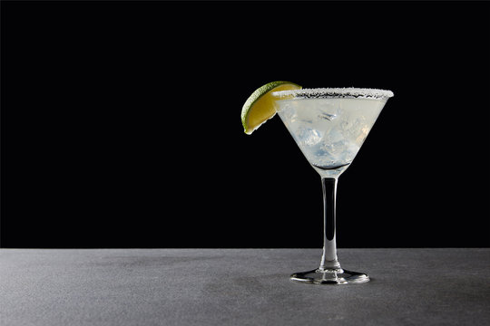 close up view of tasty margarita cocktail with lime and ice on tabletop on black