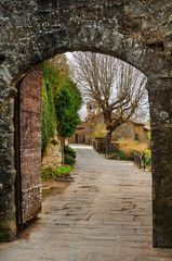 Cortona medieval historic center seen through Porta Montanina ancient gate, in Tuscany