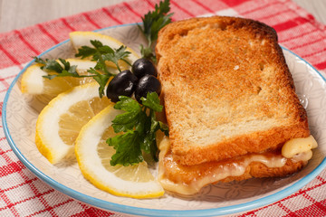 Good and delicious food and beverages for breakfast. Toast with butter and cheese, slices of lemon and olives on plate