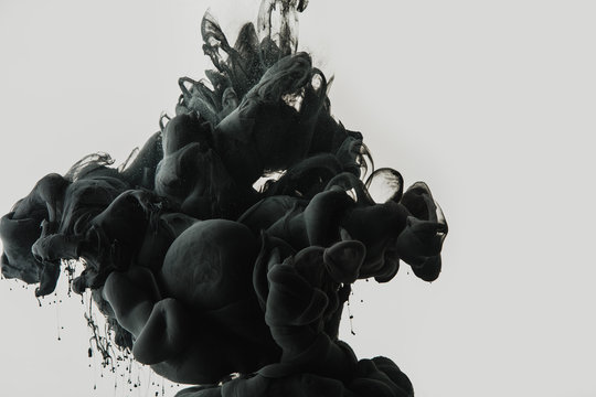 close up view of black paint splash in water isolated on gray