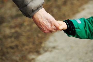 grandmother holding grandchild hand while walk on road