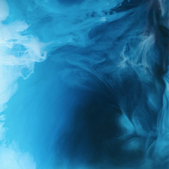full frame image of mixing of blue, black and white paints splashes  in water