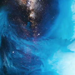 full frame image of mixing blue and black paint splashes in water with universe background