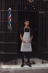 Barber standing with hands in pocket at the entrance of his shop