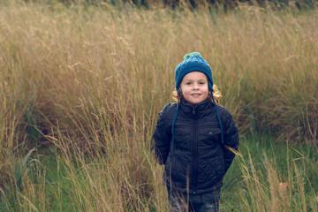 Cheerful little boy standing in grass