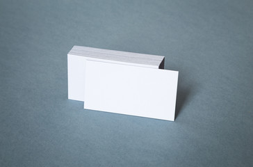 Blank white business cards with shifted front cardon a grey background