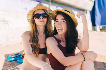 Two young cheerful girls sunbathing on the beach