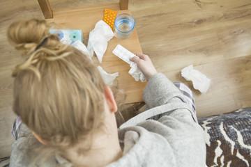 Woman taking medicine capsules at home