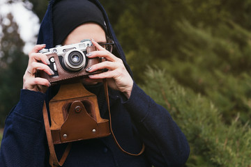 Young blonde woman in black hat and hoodie holding retro photo camera and taking photo in coniferous forest. Journalism concept.