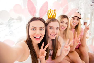 Attractive, charming, cheerful, pretty, stylish girls with crown, bunny ears, eye mask on heads shooting selfie on front camera showing v-sign, having theme party, dress code, sitting on bed