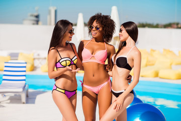 Three beautiful sexy sexual slim slender charming excited carefree relaxed stylish joy enjoy fun attractive pretty hot girls in colorful bikini having conversation near swimming pool sunshine