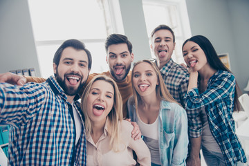 Self portrait of stylish foolish comic attractive crazy funny economists, students, financiers, lawyers in casual outfit shooting selfie on front camera showing tongue out, embracing