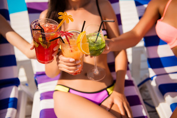 Three ladies cheering with tasty nectars with ice cubes, with black straws, palms decoration, sun tanning on striped beach chairs, sun shines, smooth tanned skin, carefree festive mode, refreshing
