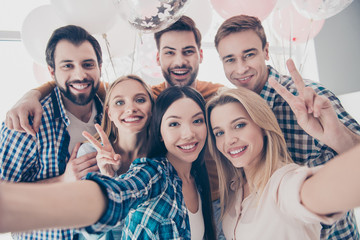 Creative, stylish, attractive, cheerful, beautiful, handsome business people having air balloons  shooting self portrait on front camera showing peace symbol two fingers celebrating event