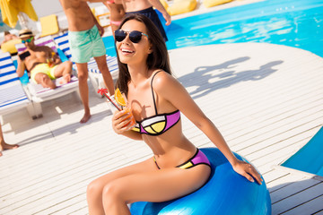 Wall Mural - Cropped close up portrait of cheerful delightful charming beautiful attractive with long brunette hair trendy colorful bikini sitting blue ball enjoying sunshine sunbathing drinking cocktail poolside
