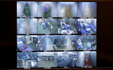 A screen showing images from security cameras is seen at Delicious Cook & Co's food factory in Narashino