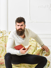 Fascinating man dressed in refined manner and reading book on upholstered sofa in bright and luxurious living room. Man, scientist, professor on thoughtful face enjoy literature. Elite leisure concept