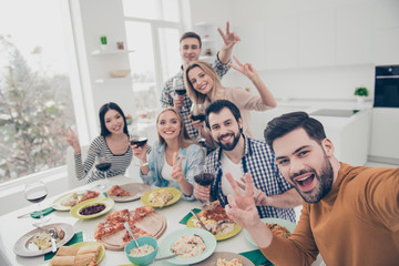 Self portrait of stylish positive cheerful best friends showing two fingers hi holding wineglasses with red wine in hands having video-call sitting at the table modern dinning room indoor