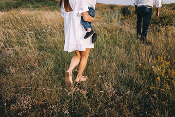 Walk beautiful young family in white clothes with a young son blond in mountainous areas with tall grass at sunset. Mother keeps son in his arms, hugging. family - this is happiness