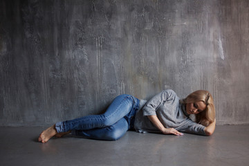 Sad woman lying on the floor. Depression and chronic fatigue. Young beautiful blonde in a gray sweater and jeans