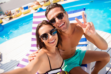 Self portrait of attractive, stylish, cheerful couple in summer glasses, spectacles showing two fingers shooting selfie on front camera sitting on lounger, sunbed, chaise-longue near swimming pool