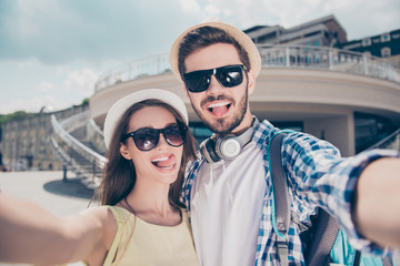 Stylish trendy attractive funny couple in caps having journey trip meeting outdoors shooting self portrait on front camera showing tongue out, beautiful woman, handsome man with headphones on neck