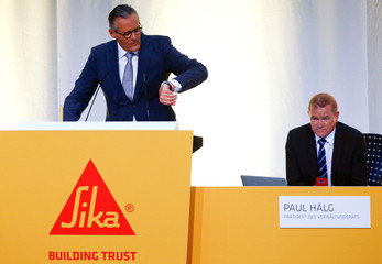 CEO Schuler sits beside Haelg, chairman of the board of Swiss chemicals group Sika, as he checks his watch during the company's annual shareholder meeting in Baar