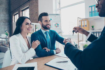 Cropped portrait of joyful, cheerful, lovely, successful couple, man shaking hands with dealer who holding a key in hand from new building, together in classic suits and sitting in work place, station