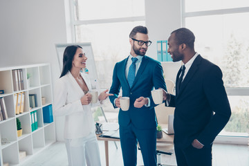 Three stylish, modern, cheerful partners in tux, tuxedo having break time, speaking during coffee time, standing in work place, station, holding mug with coffee in hands, men with bristle, in glasses